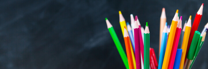 Back to school! Colored pencils in a glass on the background of the school chalkboard