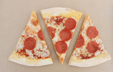 Pepperoni Pizza Slices Isolated on Empty Brown Craft Paper Background Top View. Simple Fast Food Banner with Pepperoni Sausage, Cheese and Tomato Sauce Pizza Slices Top View with Empty Copy Space