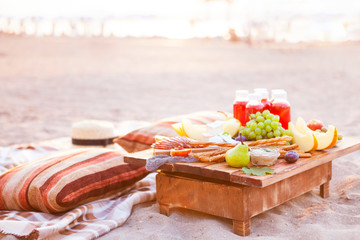 Aluminium Prints Picnic Picnic on the beach at sunset in the style of boho. Concept outdoors evening healthy dinnner with fruit and juice