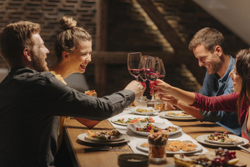 Friends making celebratory toast at dinner table