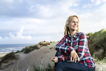 Smiling woman sitting in dunes