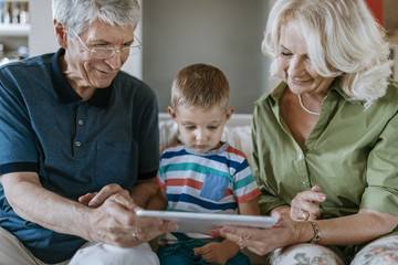 Grandparents and grandson at home sitting on couch sharing tablet