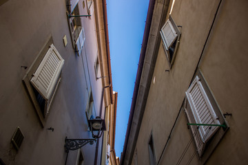 beautiful vintage urban concept of narrow street in old city district and two buildings from below with closed white windows shutters without people and summer colorful atmosphere