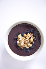 Acai bowl with heart shape of blueberries on the white table