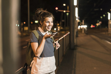 Portrait of young woman on the phone waiting at station by night