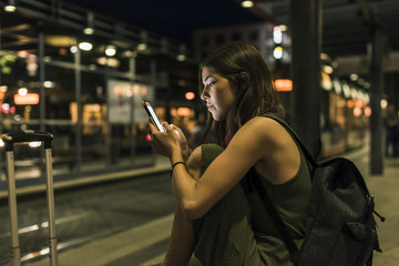 Young woman with backpack and baggage waiting at the station by night using cell phone