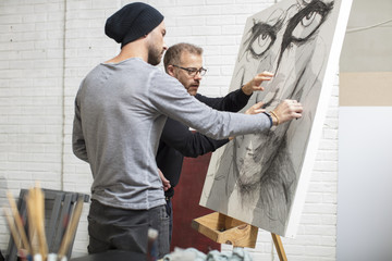 Artist discussing drawing with man in studio