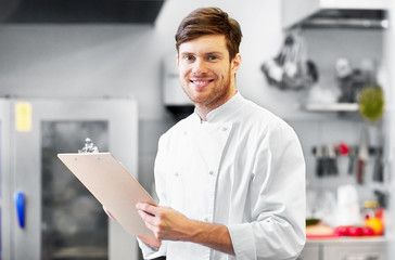 cooking, profession and people concept - happy smiling male chef cook writing to clipboard and doing inventory at restaurant kitchen