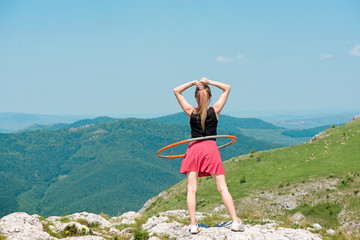 Young woman in pink skirts rotates hula hoop at the mountain top on beautiful nature background. Healthy lifestyle and love for fitness and sport. Freedom and fresh air outdoors