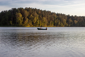 Family in a boat at sunset on the calm waters of a lake and behind a forest enjoying life