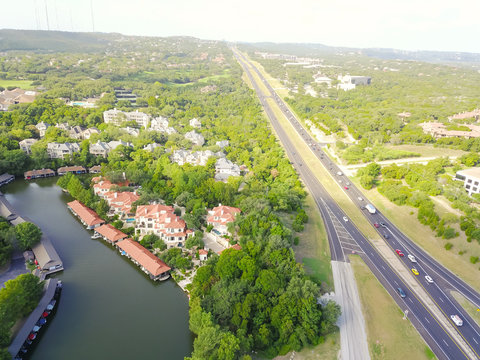 Aerial view lake mansions with boat storage green trees near highways