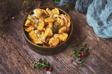 Raw wild mushrooms chanterelles in bowl on old wooden background.
