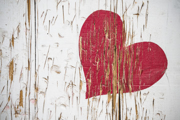 Red heart scratched in wood in red color