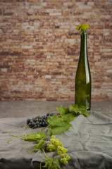 Fototapeta butelka do wina otoczona przez winorośl obraz