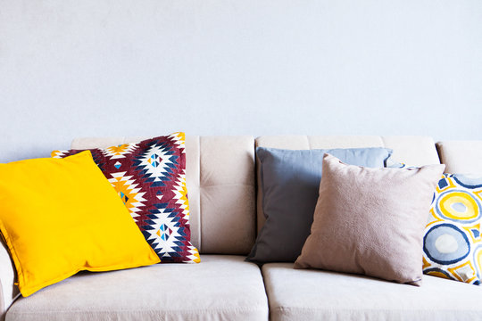 Multi-colored pillows on a beige fabric sofa, the concept of home comfort and cozy, copy space, close up