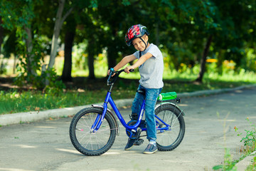 Little boy learns to ride a bike in the park near the home. Portrait of a cute kid on bicycle. Happy smiling child in helmet riding a cycling.