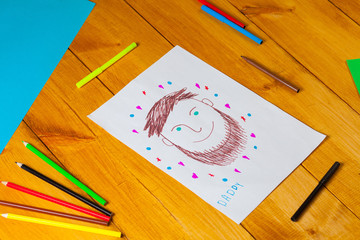 Child draws a portrait of his dad on christmas. The little boy did the drawing with pencil and marker on father's day.