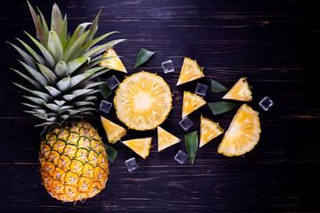 Fresh pineapple on black wood, black background.