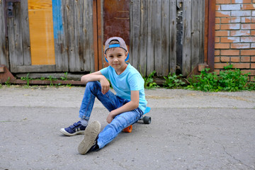 Beautiful young boy sitting on a skateboard. Children ride on the Board in the street. Active lifestyle, sports, training. Kid was tired after riding.