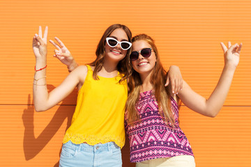 fashion, leisure and people concept - smiling teenage girls in summer clothes hugging and showing peace hand sign outdoors