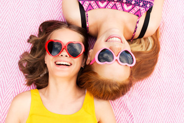 summer fashion, leisure and valentines day concept - smiling teenage girls in heart shaped sunglasses lying on picnic blanket