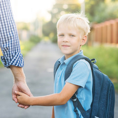 Father holding little son's hand. Little schoolboy with backpack smiling, looking at the camera and going to school. Back to school concept.