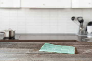 Blurred background. Modern defocused kitchen with wooden tabletop and space for you design.