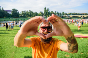 Hipster happy celebrate event picnic fest or festival. Cheerful fan love summer fest. Man bearded hipster in front of crowd people show heart gesture riverside background. Urban event celebration