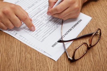 close-up partial view of person signing insurance form at wooden table with eyeglasses