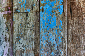 Wooden wall with blue paint is severely weathered and peeling. Cracked paint wooden wall. Wood slats rustic shabby empty background. Paint peeled weathered surface. Grunge facade wallpaper.