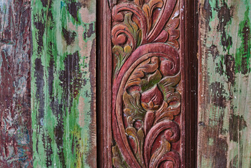Floral wood carving.  Ancient motifs are used to decorate furniture that is made of teak. Details of a  wood carving art. Part of an old shabby wooden wall with a pattern. Abstract background.