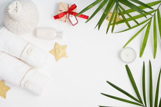 Christmas spa tropical mockup: white towels, Thai massage bags, golden stars and green fern leaves with gift boxes on background. New year gift concept. Text space