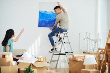Young Asian lady showing boyfriend where to hang nice picture while decorating new apartment together