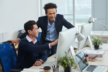 Adult Asian man smiling and pointing at financial data on computer monitor for colleague while working in office together