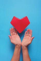 Heart health or Valentine's day concept. Hands holding red paper heart. Origami. Paper cut style. Toned