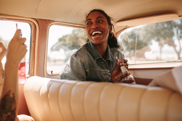 Cheerful woman traveling by car with friends