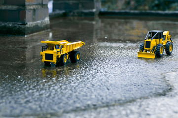 There are forklifts and truck toys next to waterlogged cement   and old brick pillars.