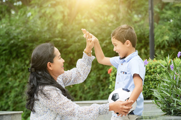 Side view of adult Asian woman smiling and giving high five to sweet boy with football ball while spending time in park together