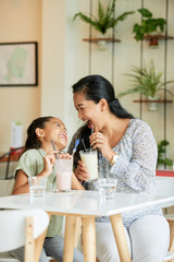 Adult Asian woman and adorable girl laughing and looking at each other while drinking delicious milkshakes in cozy cafe