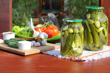 Canning cucumbers with spices in glass jars on a wooden table in front of the greenhouse.