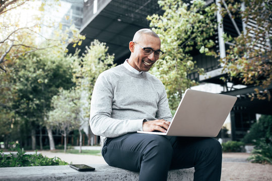 Businessman working on laptop computer sitting outdoors