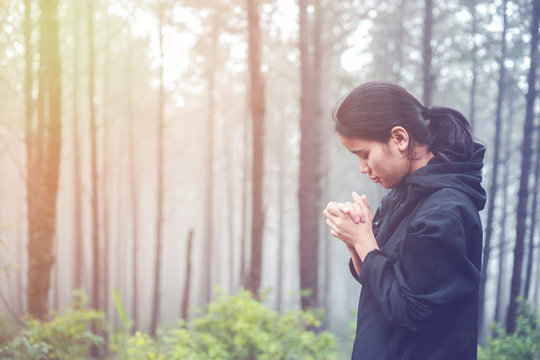 The woman is praying to God in the forest.
