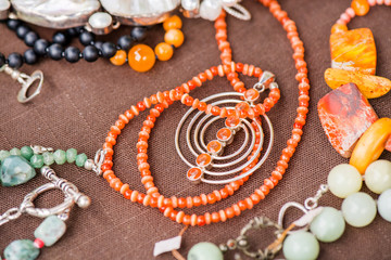 Serdolik (carnelian) stone necklace laying on natural brown linen tablecloth. Yashma, orange jasper, onyx gemstones around. Healing, powerful energy for crystal therapy treatments. Esoteric background