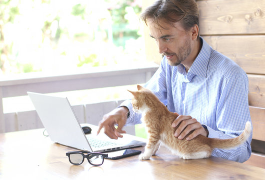 Young businessman is working on laptop with his cat on an open terrace. Freelance or home office concept