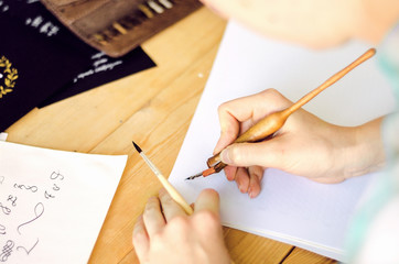 A girl calligrapher paints pen on white paper behind her working wooden table.