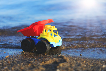 Toy truck on the gold sandy beach. Colorful car on the seashore in front of the water waves. The image of camion parked in sand. Conceptual picture of beach vacation, lost or child missing.