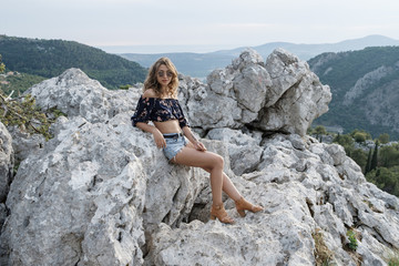 Young stylish curly blonde woman in shorts and crochet tops and sunglasses sits on the rock  against the backdrop of mountains and sea in Montenegro.
