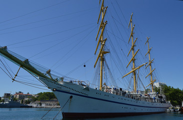 Old yacht with lowered sails moored in the port