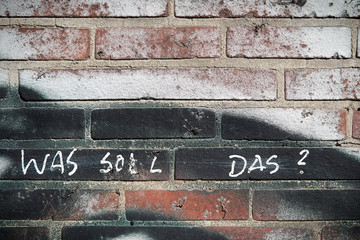 """Wand aus Ziegelsteinen mit der Aufschrift """"was soll das ?"""""""