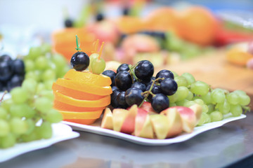 close up.plates with grapes and fruits on blurred background